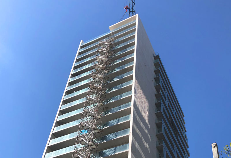 Precast concrete cross wall construction techniques with precast architectural sandwich panels and balcony units