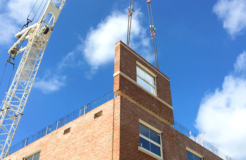 PCE's brick finished sandwich panel being craned into place at Mount Oswald