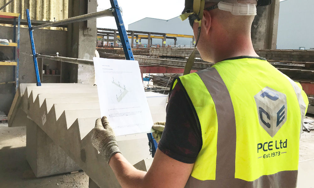 A handrail being pre-assembled to a precast concrete stair unit offsite
